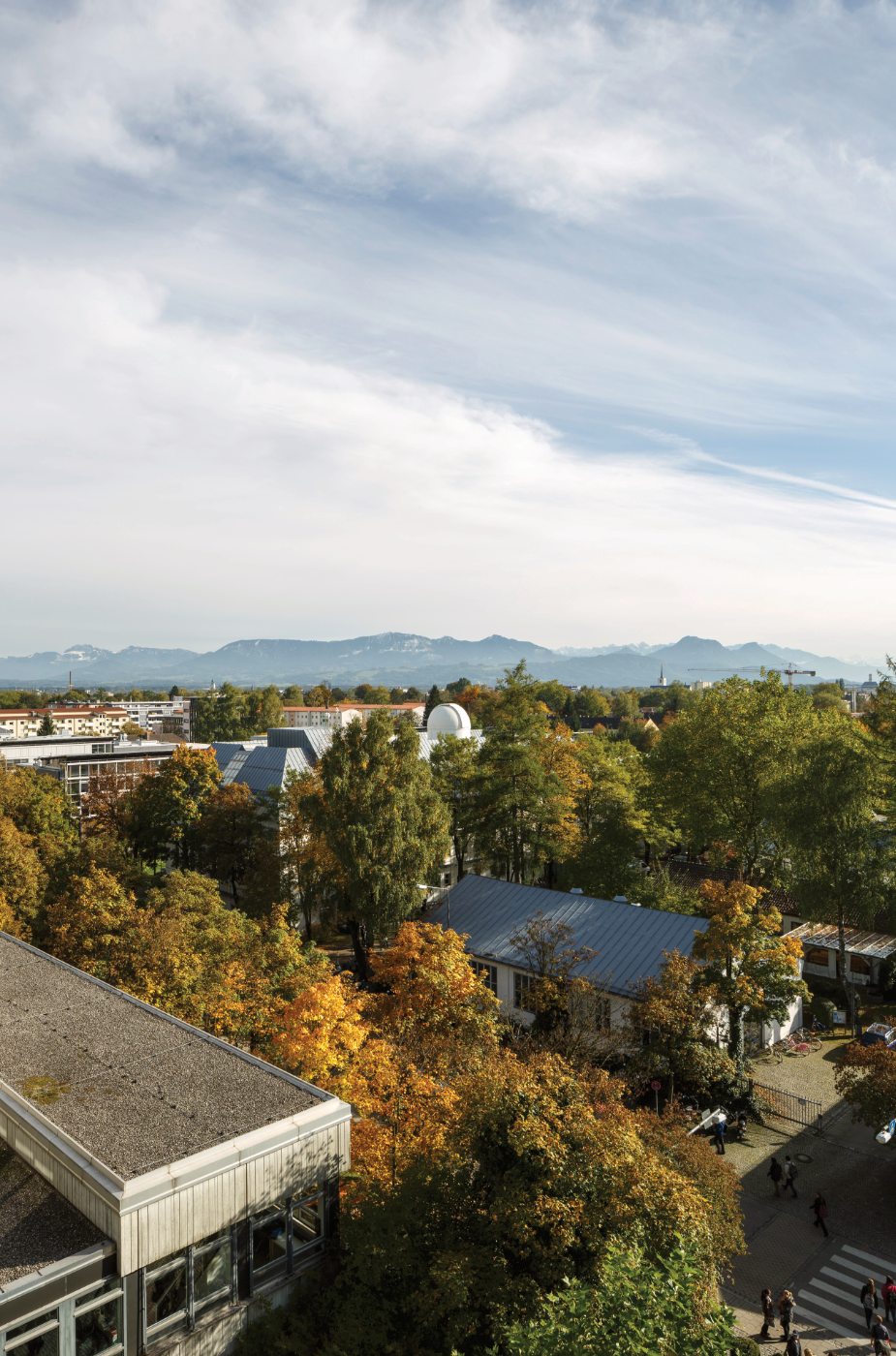 picture from above the Rosenheim Technical Univercity of applied scienes, showing a beautiful view with many trees an the mountains in the backround